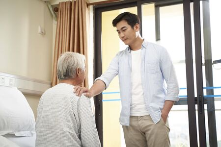 young asian adult son visiting talking to senior father in nursing home or hospital ward