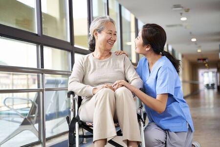 Freundliche Pflegekraft des Pflegeheims, die mit einer asiatischen Seniorin im Flur spricht