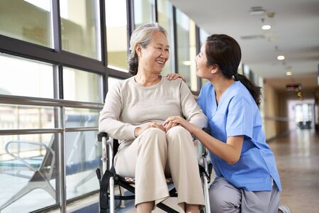 friendly staff caregiver of nursing home talking to asian senior woman in hallway