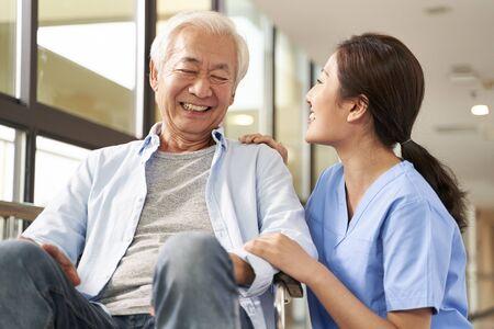 Junge freundliche asiatische Pflegerin, die mit einem glücklichen älteren Mann im Flur des Pflegeheims plaudert Standard-Bild