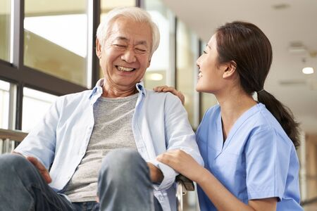 young friendly asian female caregiver talking chatting to happy senior man in hallway of nursing home
