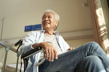 asian old man sitting in wheel chair in nursing home or hospital ward looking happy and content Zdjęcie Seryjne