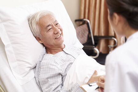 young asian doctor talking to senior patient at bedside in hosptial ward