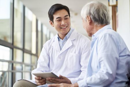 friendly smiling young asian doctor talking and explaining test result to elderly patient in hospital