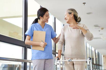 happy senior asian woman talking to physical therapist in rehab center Archivio Fotografico