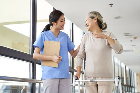 happy senior asian woman talking to physical therapist in rehab center Banque d'images