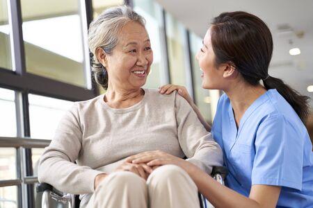 friendly caregiver of nursing home talking to asian senior woman in hallway Reklamní fotografie