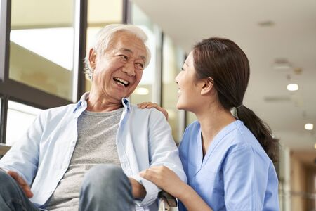 young friendly asian female caregiver talking chatting to happy senior man in hallway of nursing home Stock Photo
