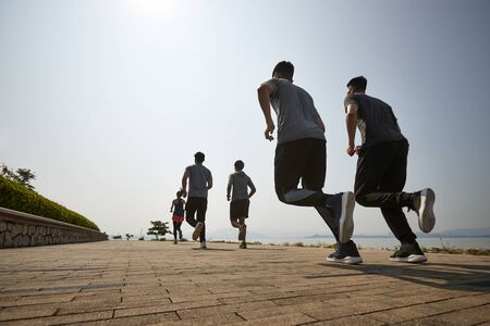 group of young asian adult men and woman running outdoors, rear and low angle view Imagens