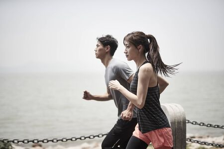 young asian man and woman running jogging outdoors by the sea, side view