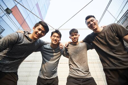 portrait of a team of young asian athletes looking down at camera smiling 版權商用圖片
