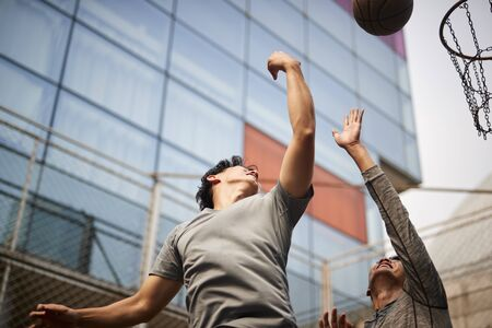 two young asian men playing basketball going up for a rebound on outdoor court