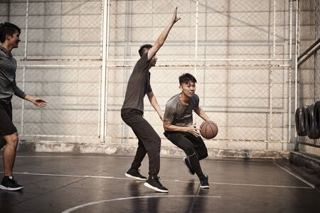 young asian adult men playing basketball on outdoor court