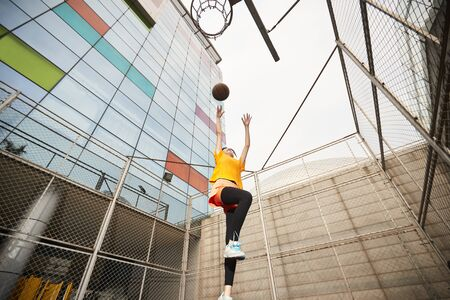young asian woman playing basketball making a shot on outdoor court