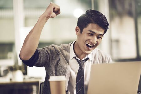young asian businessman waving fist celebrating success while looking at laptop computer in office