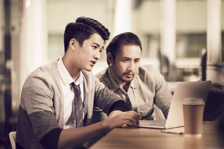 two young asian business men entrepreneurs working together in office using laptop computer