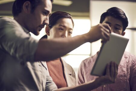 three young asian businessmen entrepreneurs working together in office looking at digital tablet