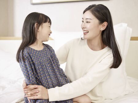 young asian mother and elementary age daughter sitting in bed relaxing playing chatting at home 版權商用圖片
