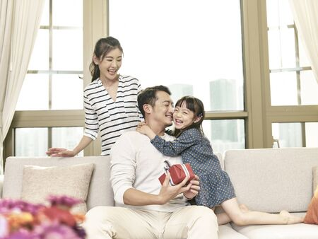 little asian girl hugging father after giving a present Stock Photo
