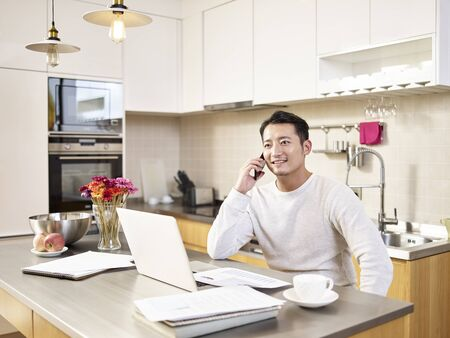 young asian business man sitting kitchen counter working at home talking on mobile phone