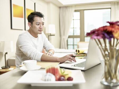 young asian business man working from home sitting at kitchen counter looking at laptop computer (artwork in background digitally altered) Фото со стока