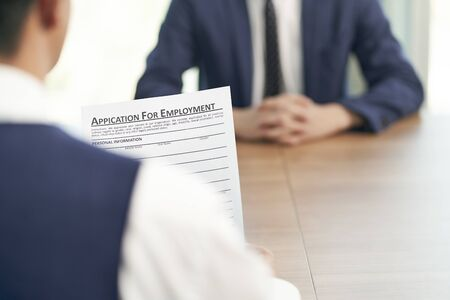 asian job seeker being interviewed by human resources manager in office, focus on the application form