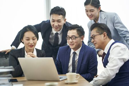 team of asian corporate executives meeting to discussing business using laptop computer
