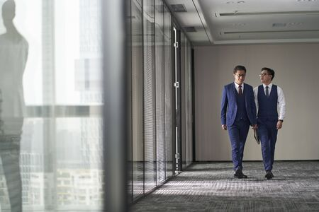 two asian corporate executives discussing business while walking in office
