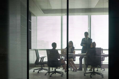 through-the-glass shot of a group of business people meeting in conference room