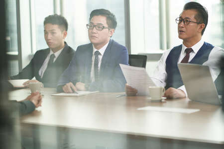 through-the-glass shot of a team of HR executives conducting an interview in company conference room