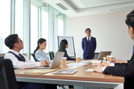 asian boss delivering a speech during meeting in company conference room