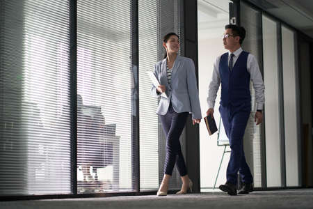 two asian business people on their way to meeting talking while walking in office