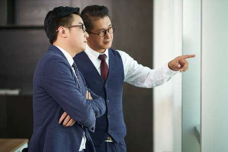 two asian corporate executives standing by window talking in office