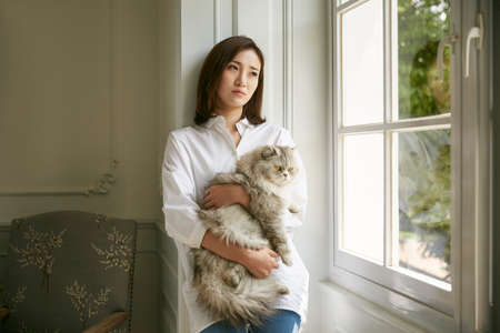 beautiful young asian woman standing by window at home holding a cat in arms looking depressed and sad