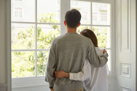 rear view of a young asian couple looking out of window during staying at home order