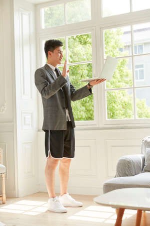 young asian business man wearing suit and shorts working from home meeting with colleagues online using video chat on laptop computer Standard-Bild