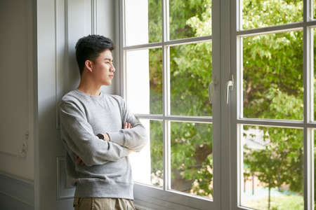 young asian man standing by window at home arms crossed Stockfoto
