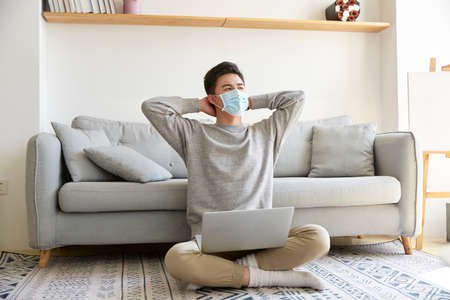young asian business man staying at home wearing mask sitting on carpet working using laptop