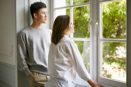 young asian couple standing by the window talking chatting during stay at home order