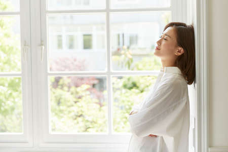 beautiful young asian woman standing by window