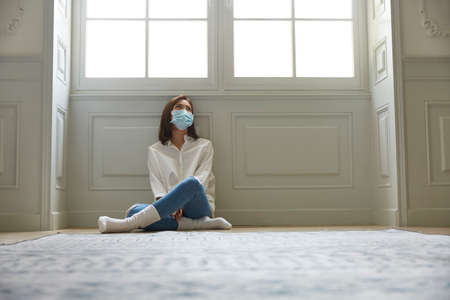 young asian woman in quarantine at home wearing facial mask sitting on floor legs crossed looking sad and depressed