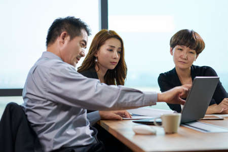 three asian corporate executives man and woman meeting in office using laptop computer