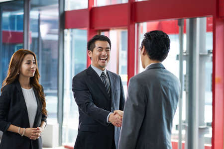 asian corporate executives shaking hands with visiting client in elevator hall of modern office building