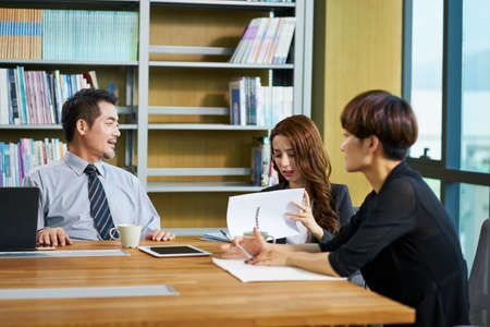 three Asian business people man and woman sitting at desk discussing business proposal in office