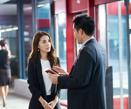 asian business man and woman standing and talking in company elevator hall using digital tablet