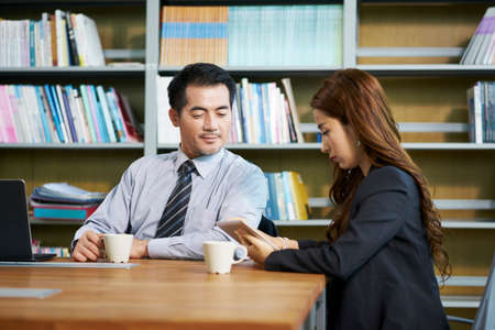 asian businessman and businesswoman sitting at desk in office discussing business using digital tablet Stock Photo