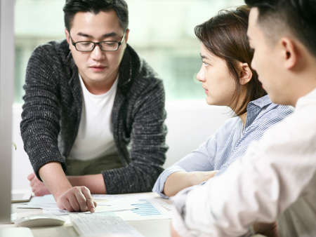 team of asian men and woman discussing business in office