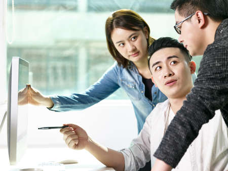 team of young asian people discussing business in office using desktop computer