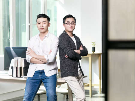 portrait of two young asian business men posing back to back in office looking at camera 版權商用圖片