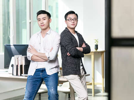 portrait of two young asian business men posing back to back in office looking at camera Stock Photo
